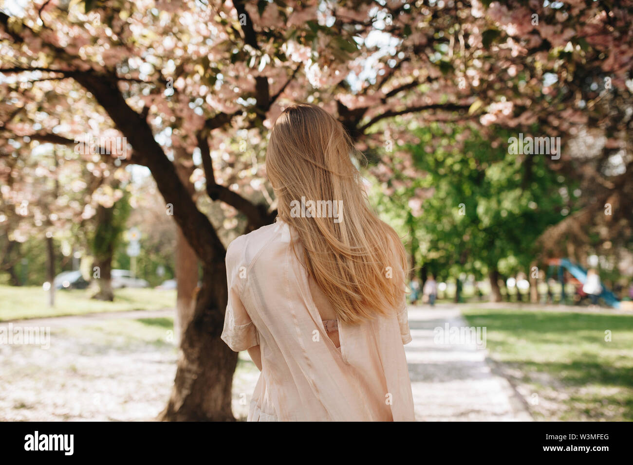 Blond haired woman by blossoming trees - Stock Image