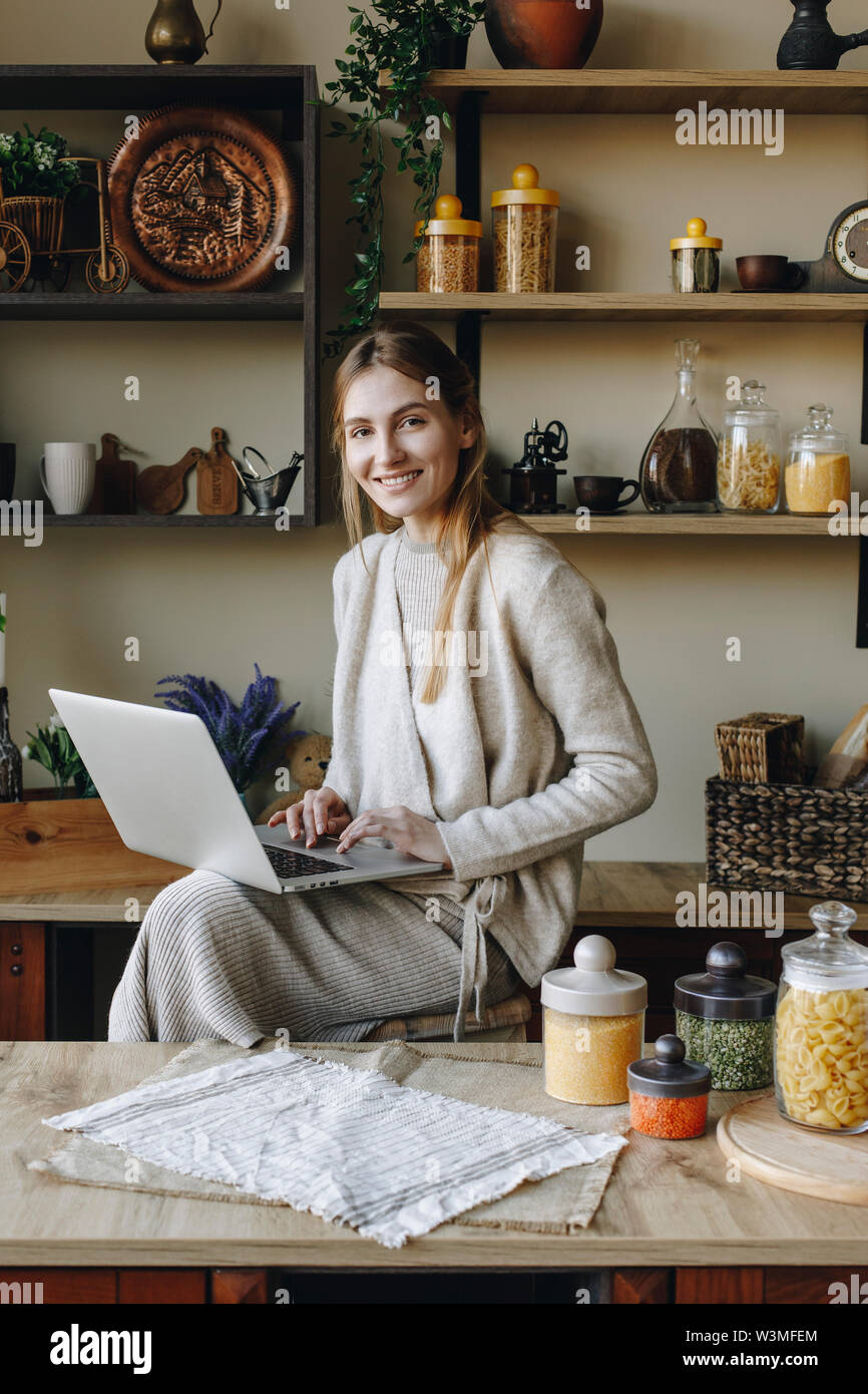 Smiling young woman using laptop in kitchen - Stock Image