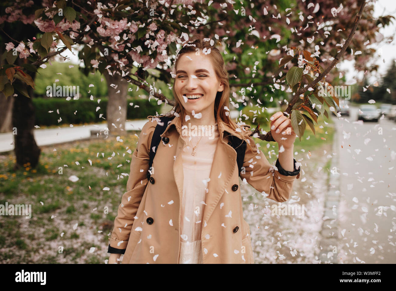 Smiling woman among falling petals from tree in bloom - Stock Image