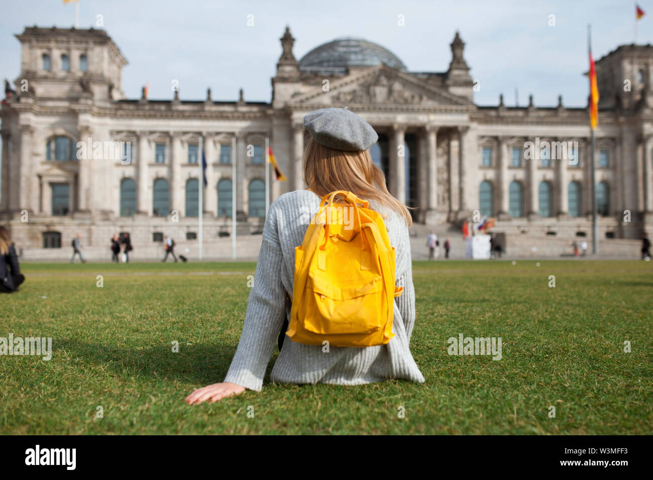 Young woman sitting in park by Reichstag in Berlin, Germany - Stock Image