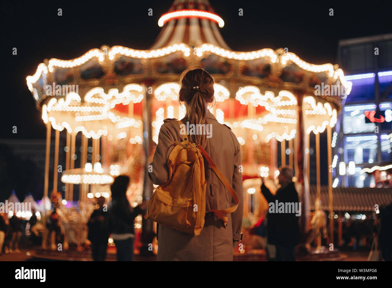 Young woman by carousel at night - Stock Image