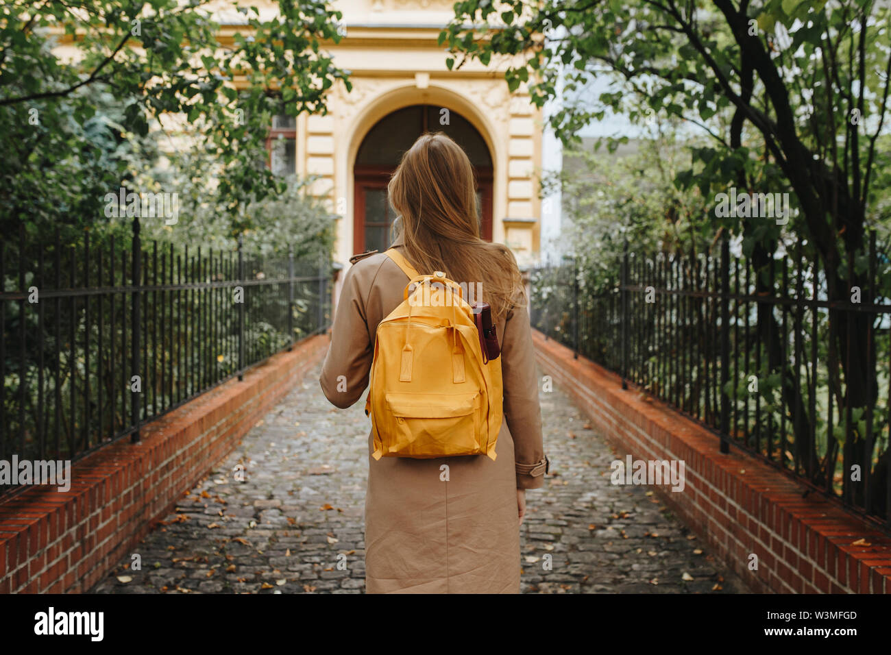 Young woman with yellow backpack walking in park - Stock Image