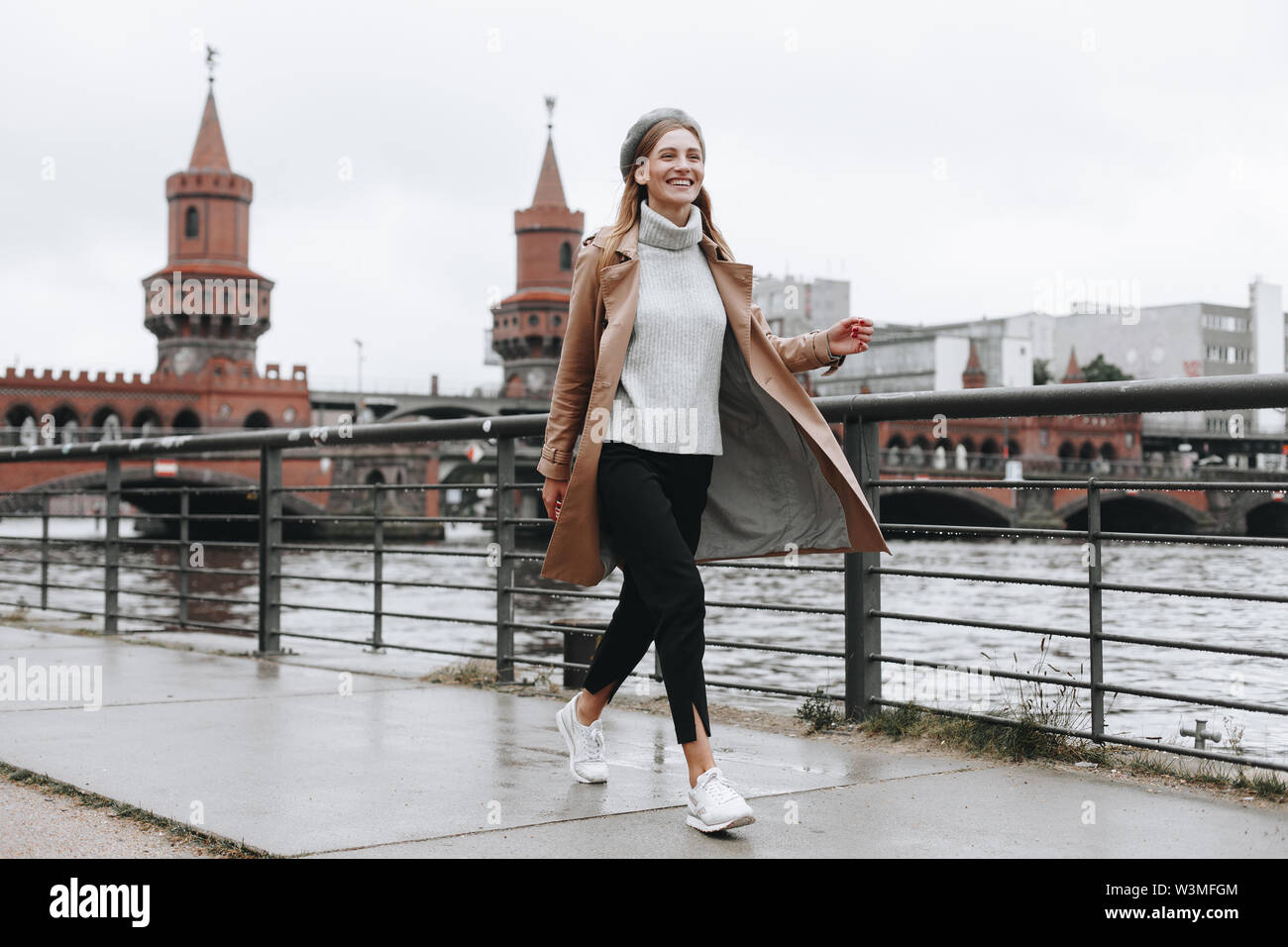 Young woman walking by river in Berlin, Germany - Stock Image