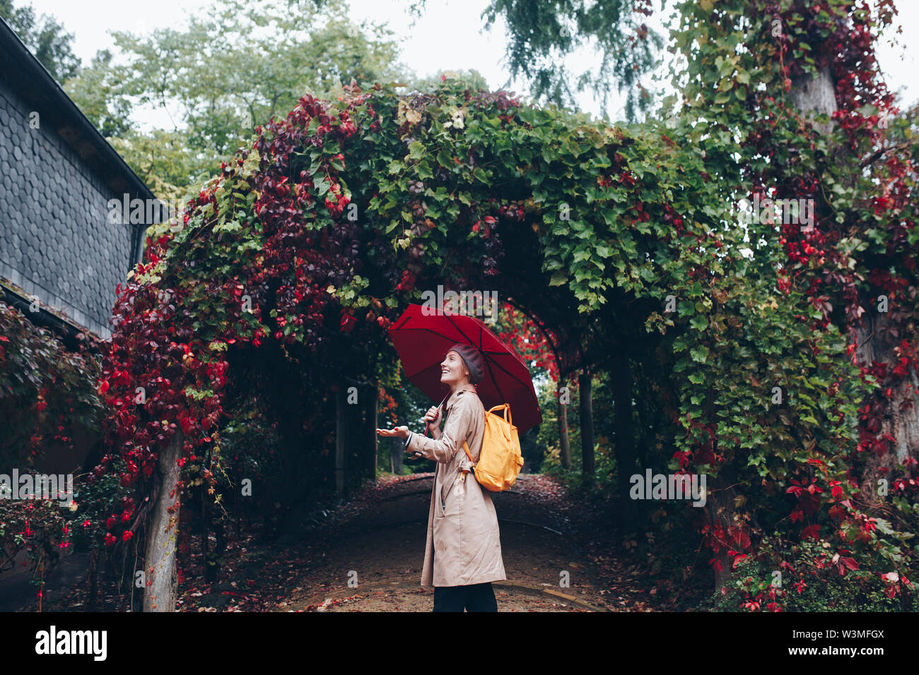 Woman holding umbrella by vine covered arch - Stock Image
