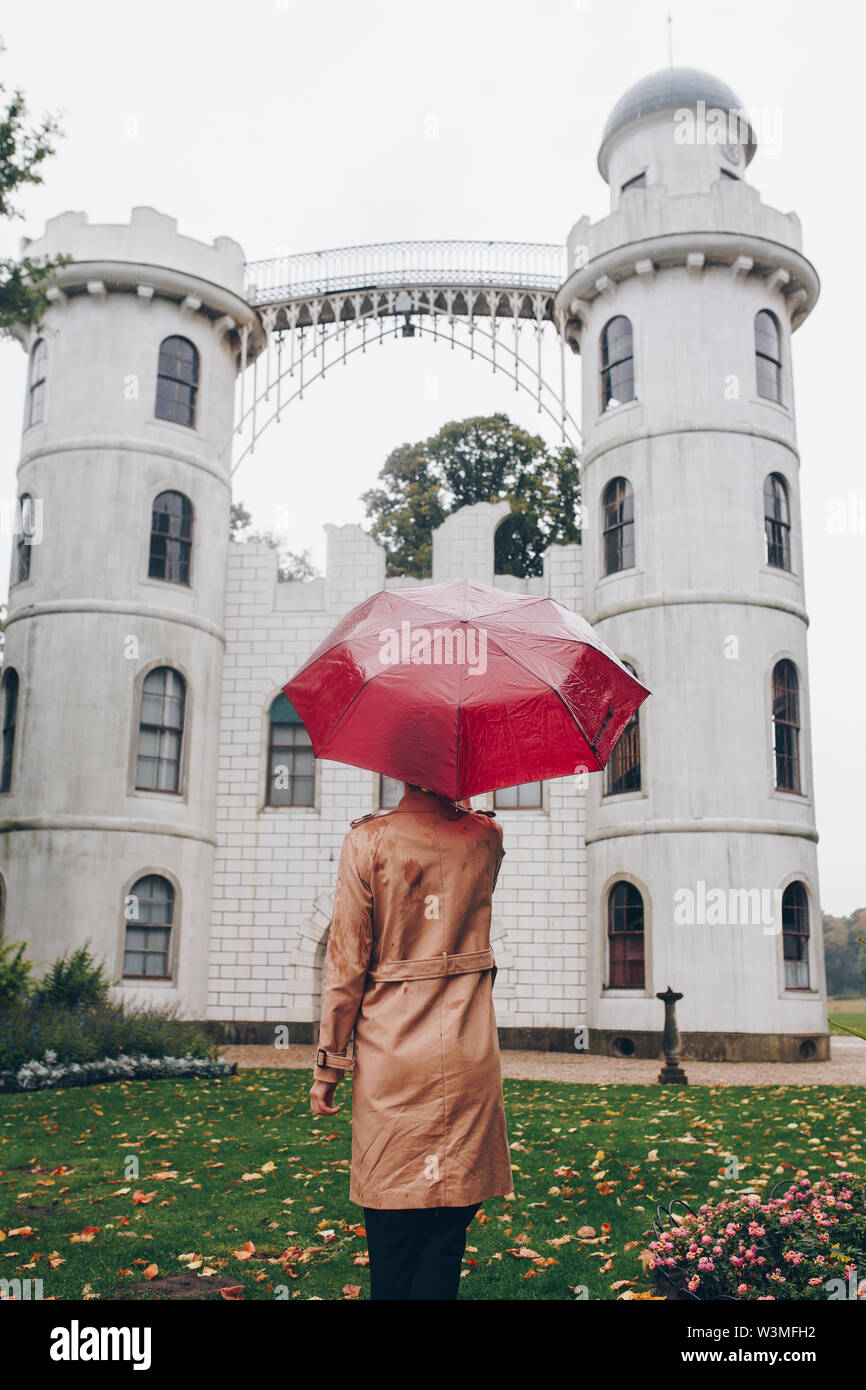 Woman holding red umbrella by Schloss Pfaueninsel in Potsdam, Germany - Stock Image