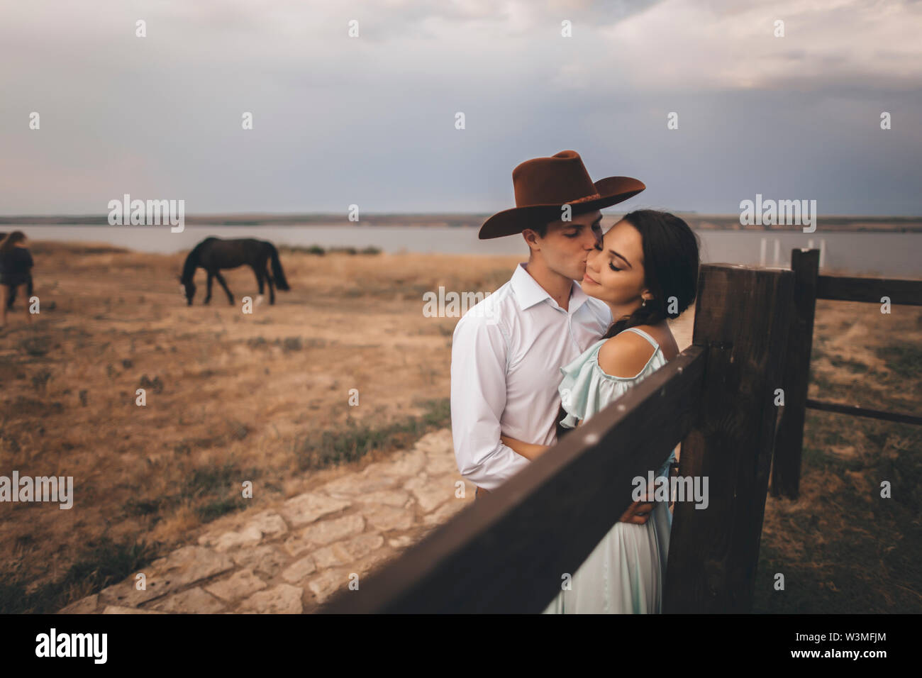 Young couple embracing in field by horses - Stock Image