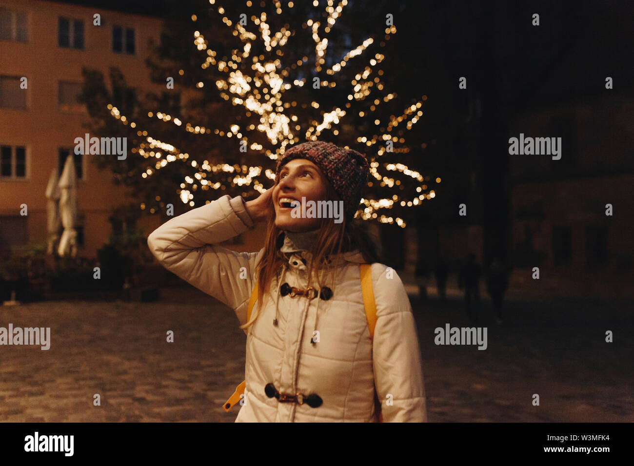 Smiling woman wearing coat by fairy lights in tree at night - Stock Image