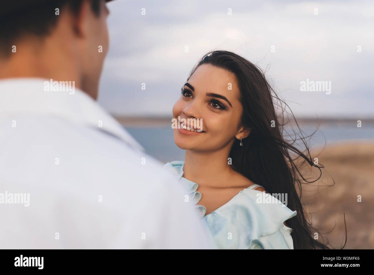 Smiling young woman looking at her partner - Stock Image