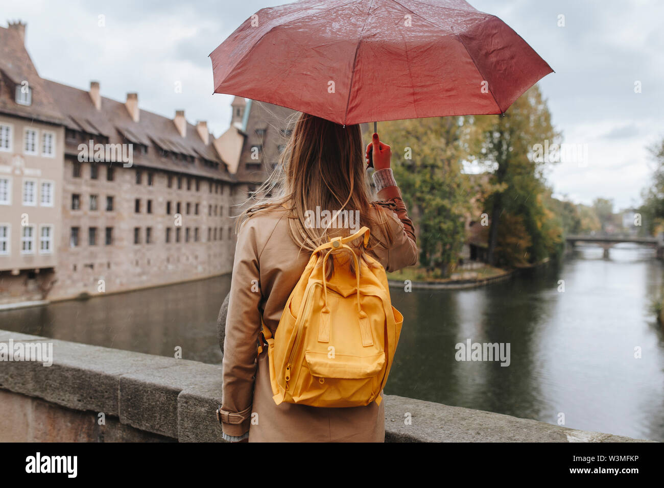 Woman wearing backpack holding umbrella by river in Nuremberg, Germany - Stock Image