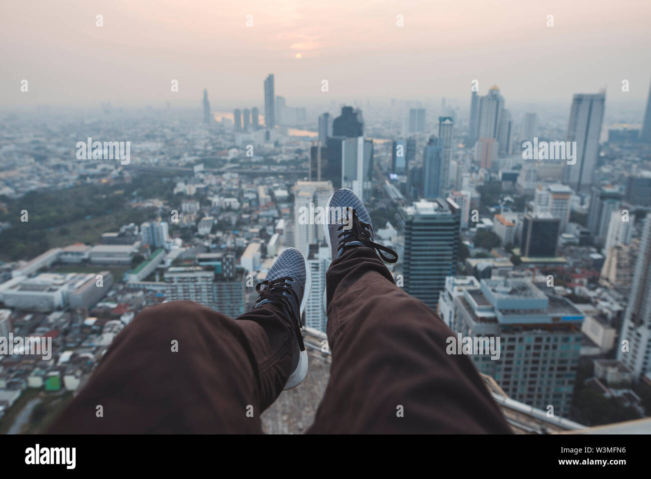 Legs of young man and cityscape of Bangkok, Thailand - Stock Image