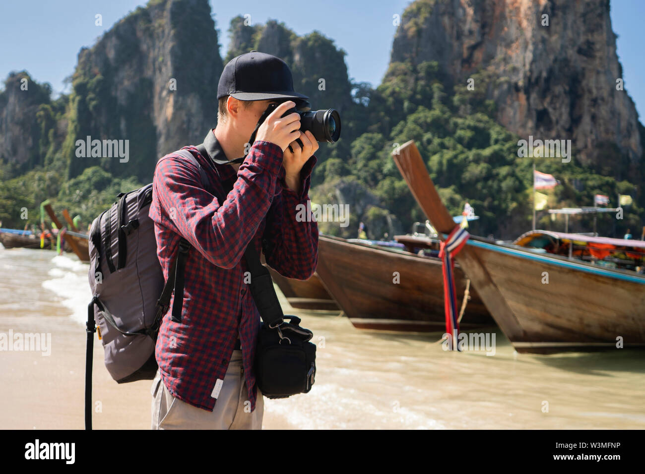 Young man photographing on beach in Krabi, Thailand - Stock Image