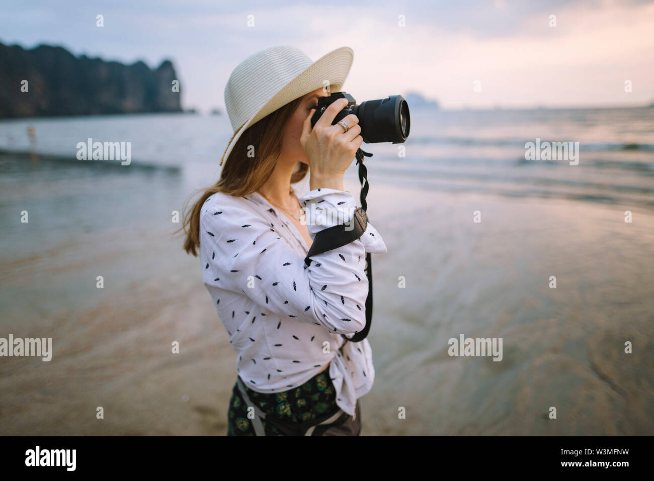 Young woman photographing on beach in Krabi, Thailand - Stock Image