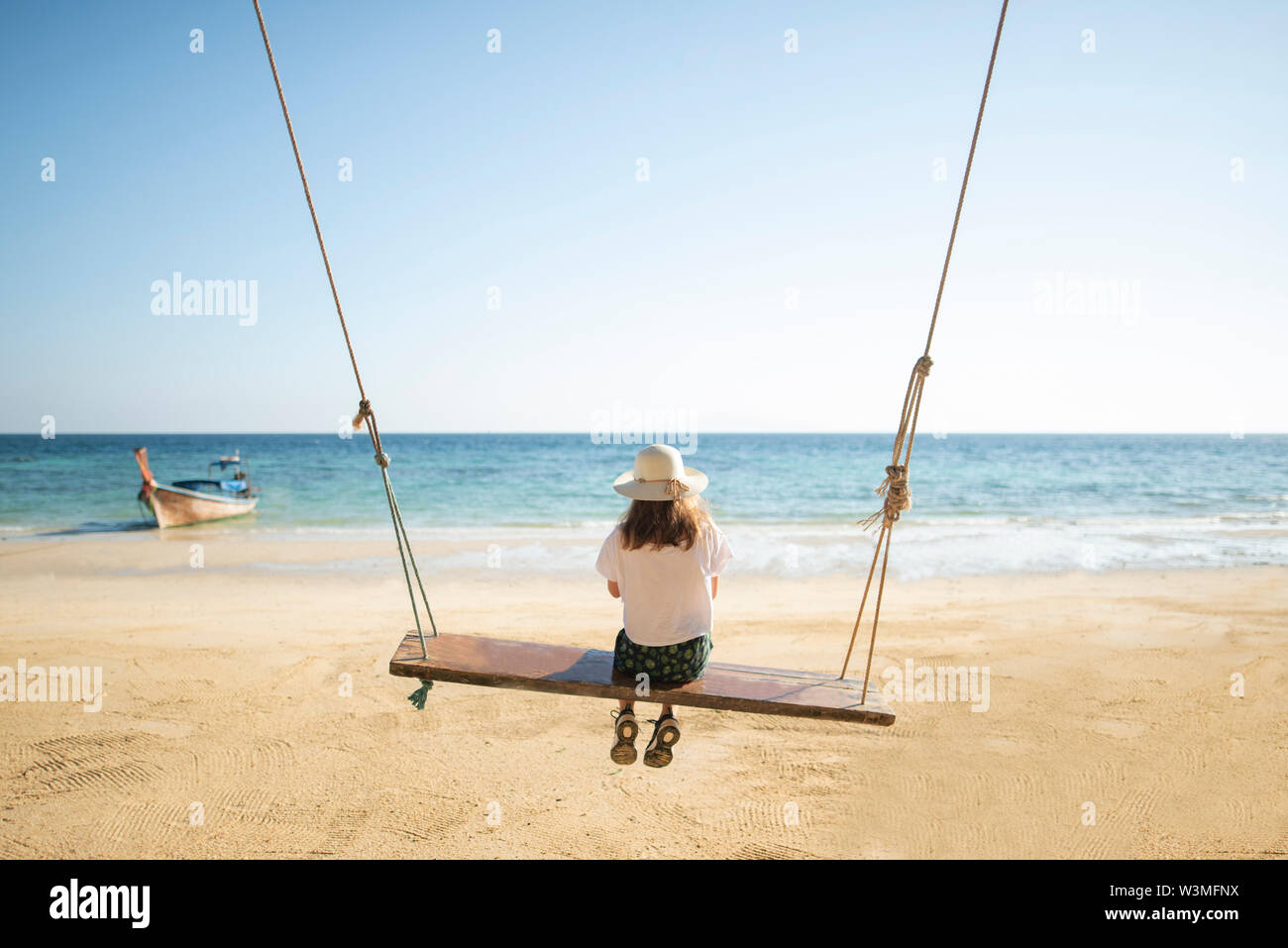 Young woman on swing at beach - Stock Image