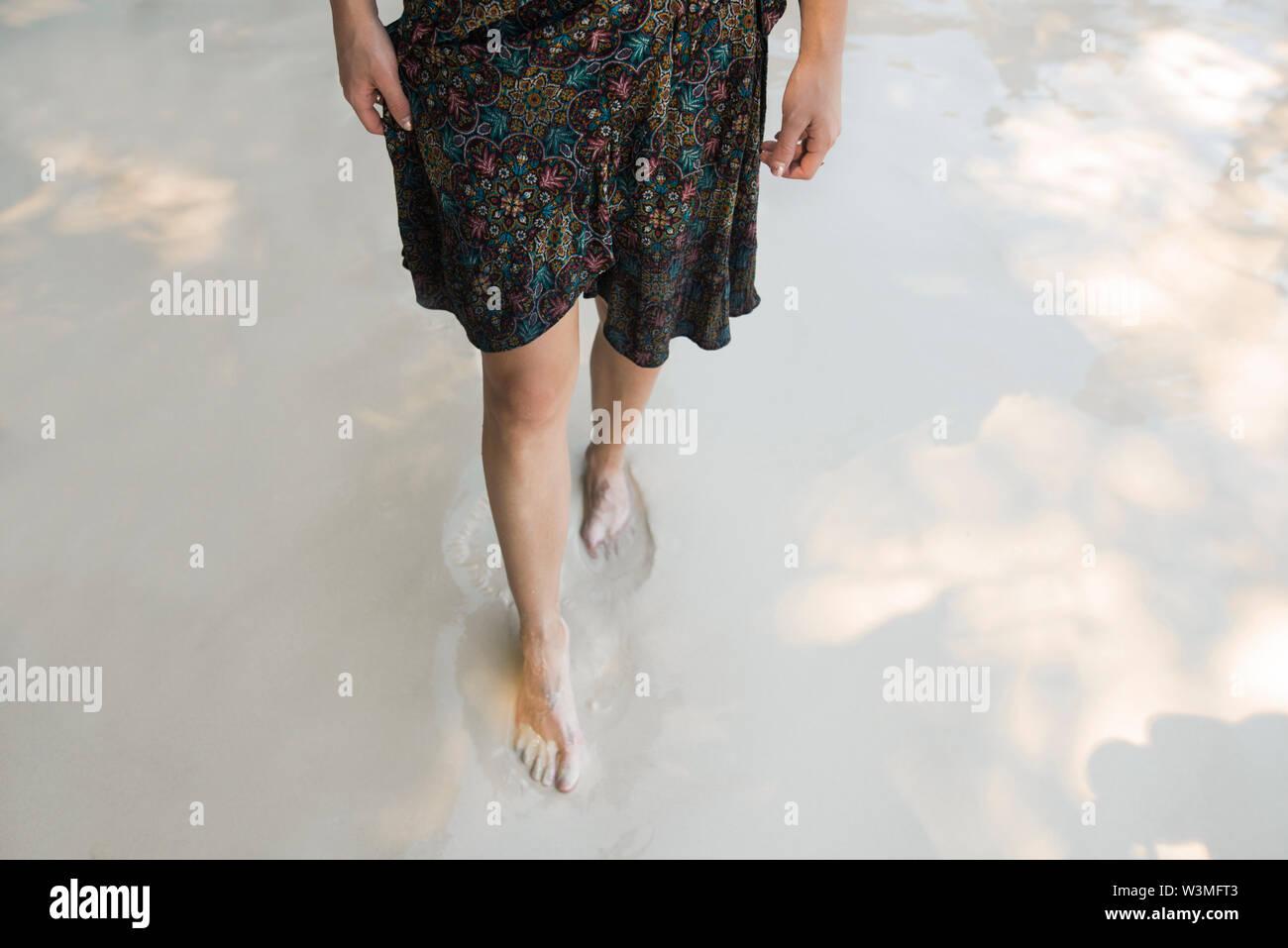 Legs of woman walking on beach - Stock Image