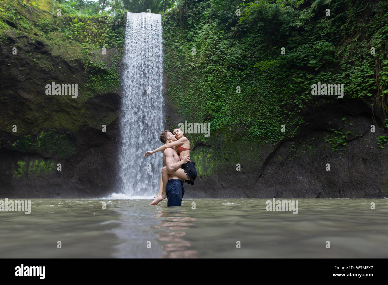 Young man carrying young woman in river by Tibumana Waterfall in Bali, Indonesia - Stock Image