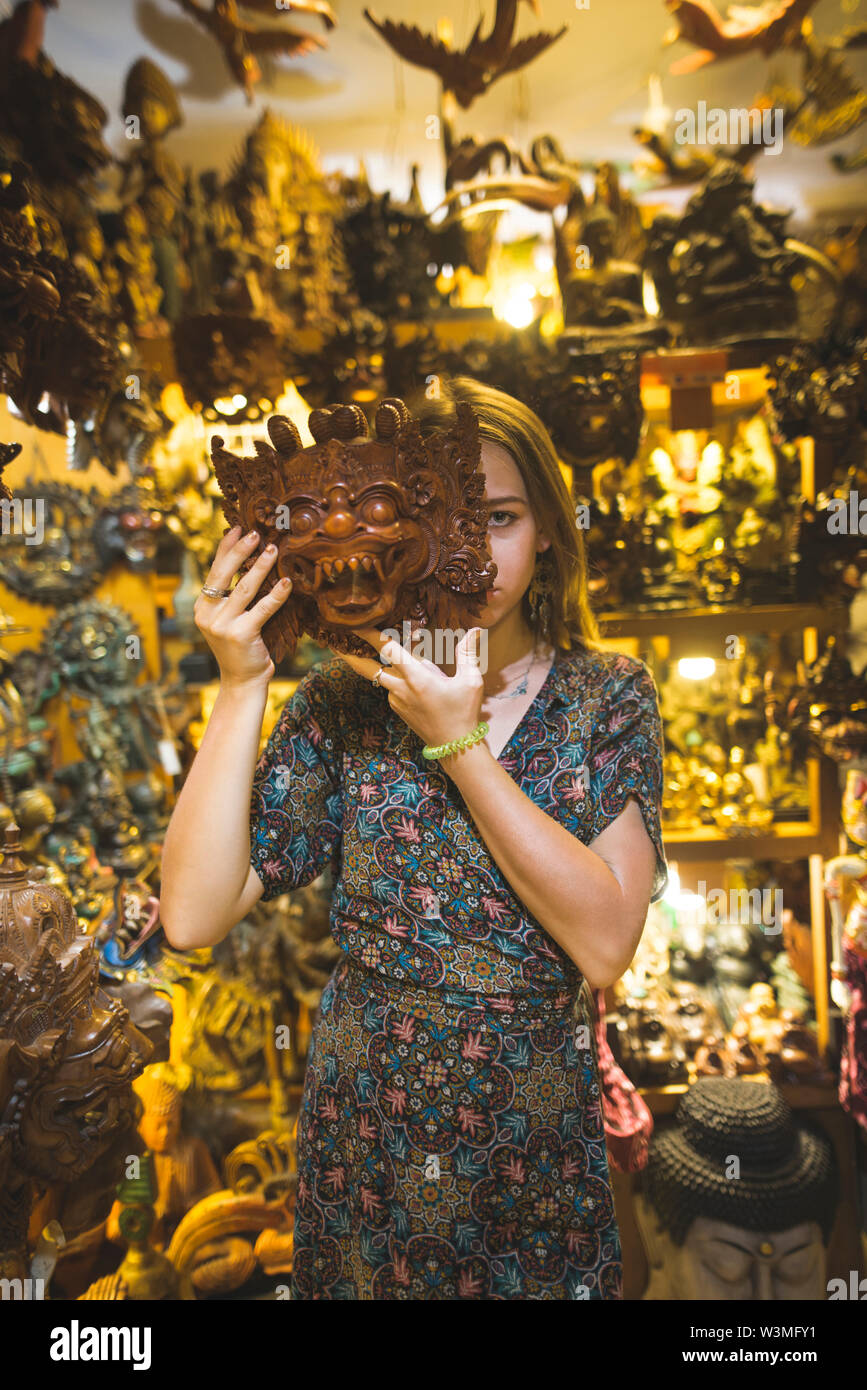 Young woman holding Barong mask in store in Bali, Indonesia - Stock Image