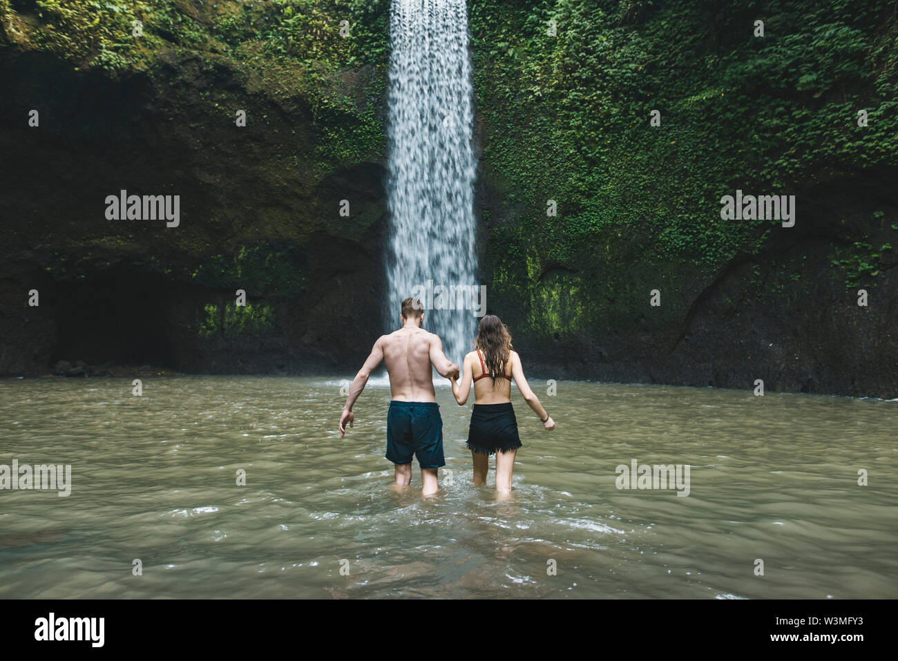 Young couple holding hands in river by Tibumana Waterfall in Bali, Indonesia - Stock Image