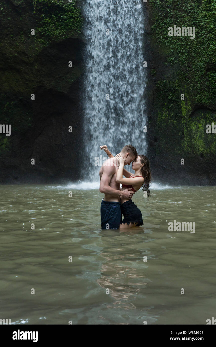 Young couple embracing in river by Tibumana Waterfall in Bali, Indonesia - Stock Image