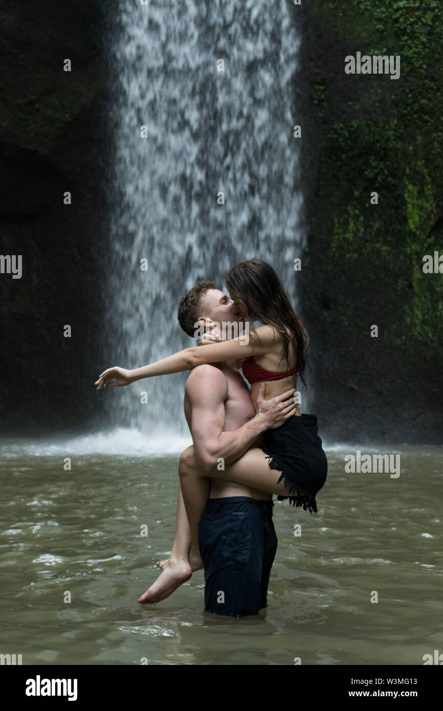 Young couple kissing in river by Tibumana Waterfall in Bali, Indonesia - Stock Image