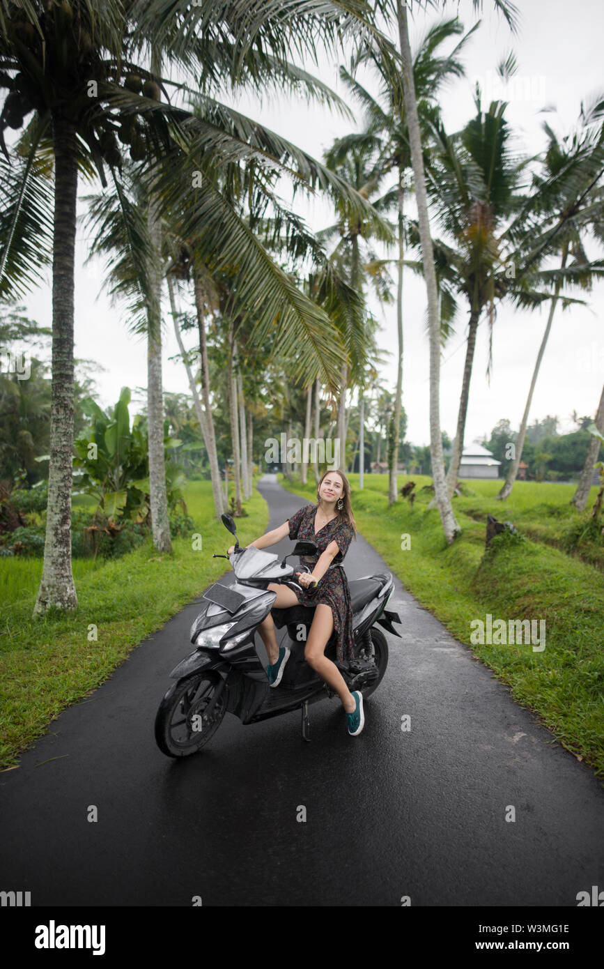 Young woman on motorcycle by palm trees in Bali, Indonesia - Stock Image