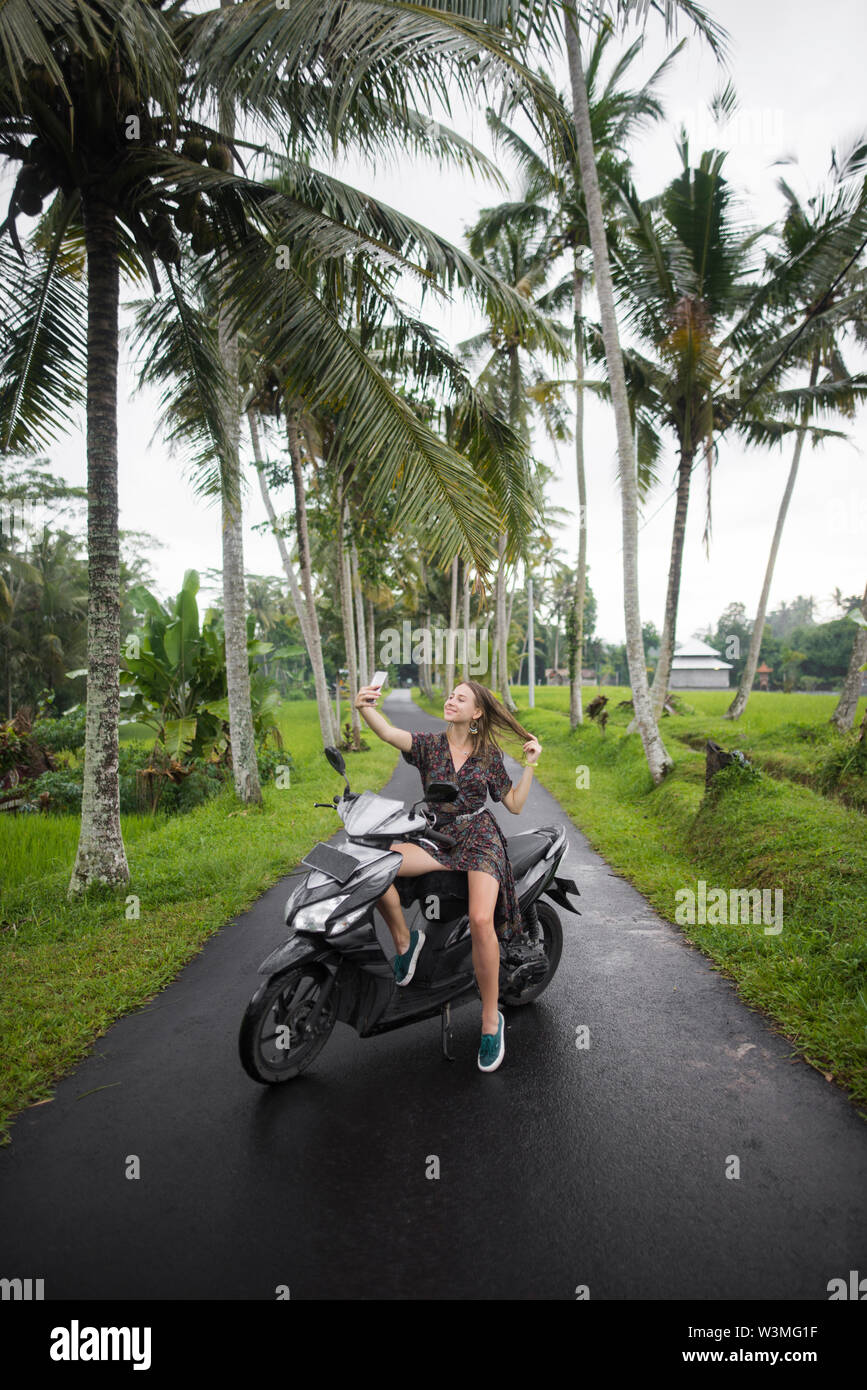 Young woman taking selfie on motorcycling in Bali, Indonesia - Stock Image