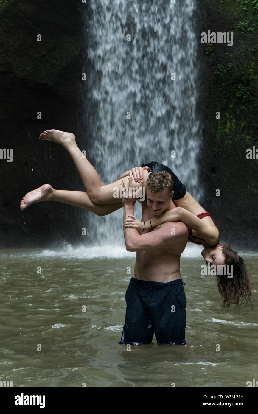 Young man carrying young woman over his shoulder in river by Tibumana Waterfall in Bali, Indonesia - Stock Image