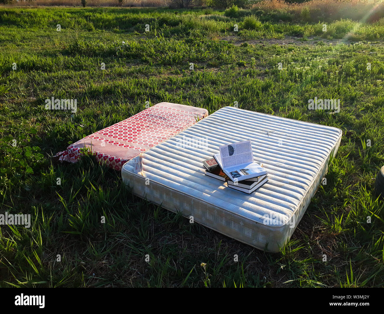 Valencia, Spain - March 30, 2019: An old abandoned mattresses in the suburbs serve to rest the homeless, who use them to read old books. - Stock Image