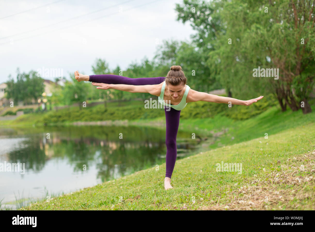 Slender Caucasian brunette girl doing yoga in summer on a green lawn by the river. - Stock Image