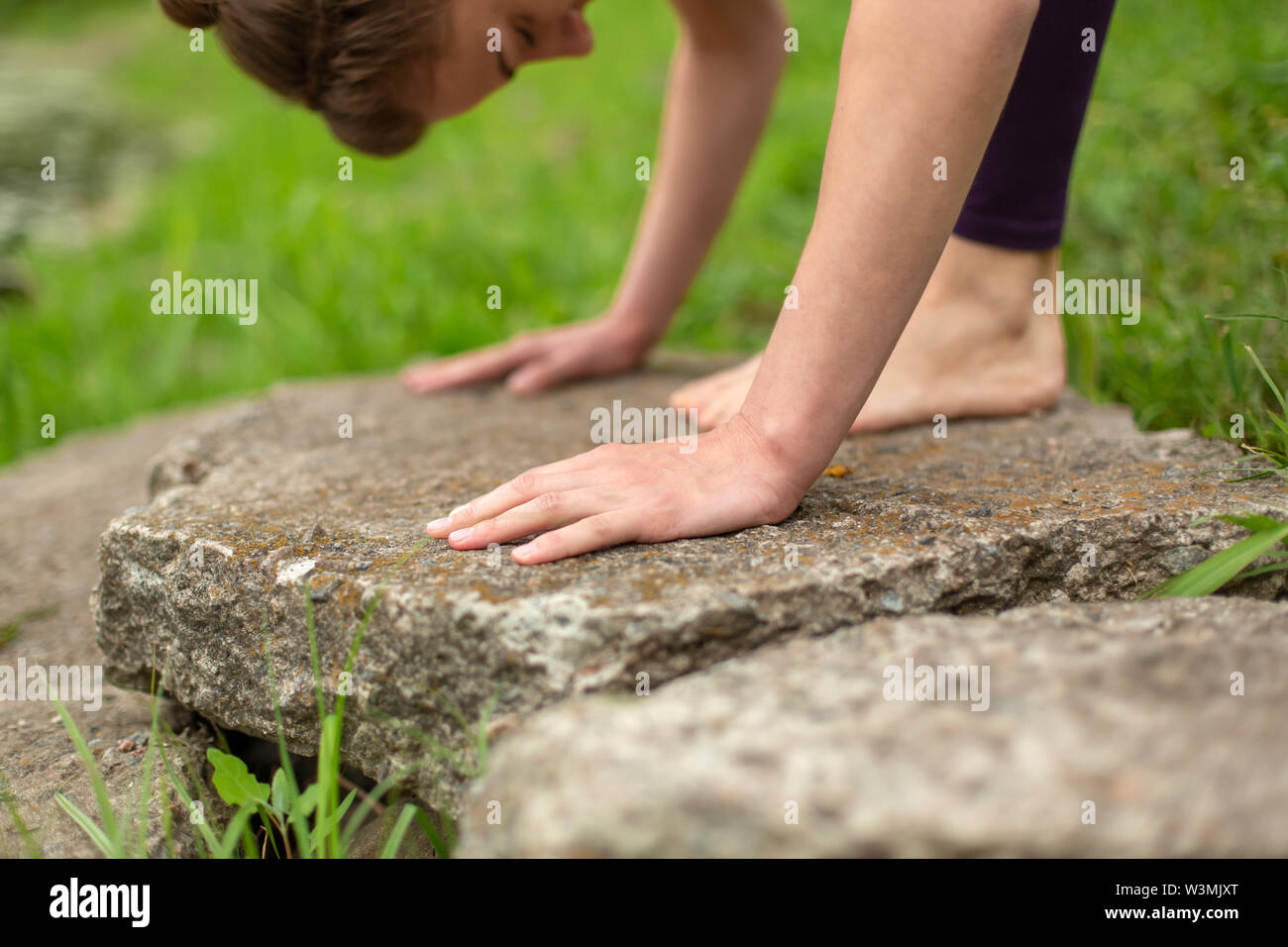 Thin brunette girl plays sports and performs yoga poses in a summer park. Green forest on the background. Woman doing exercises on the stone, hands an - Stock Image