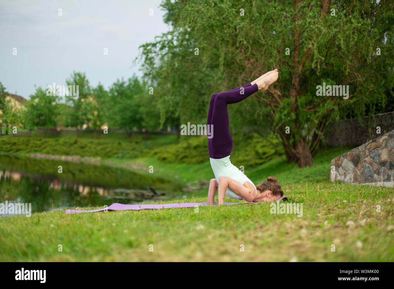 Slender young brunette yogi performs complex yoga exercise on green grass in the summer on a background of nature. - Stock Image