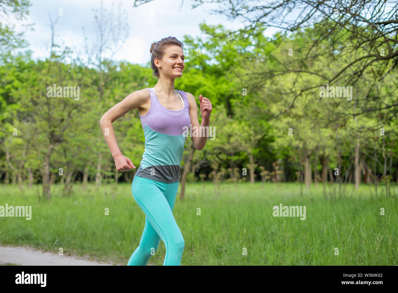 Sports brunette girl jogging in the park. Green forest on the background. - Stock Image