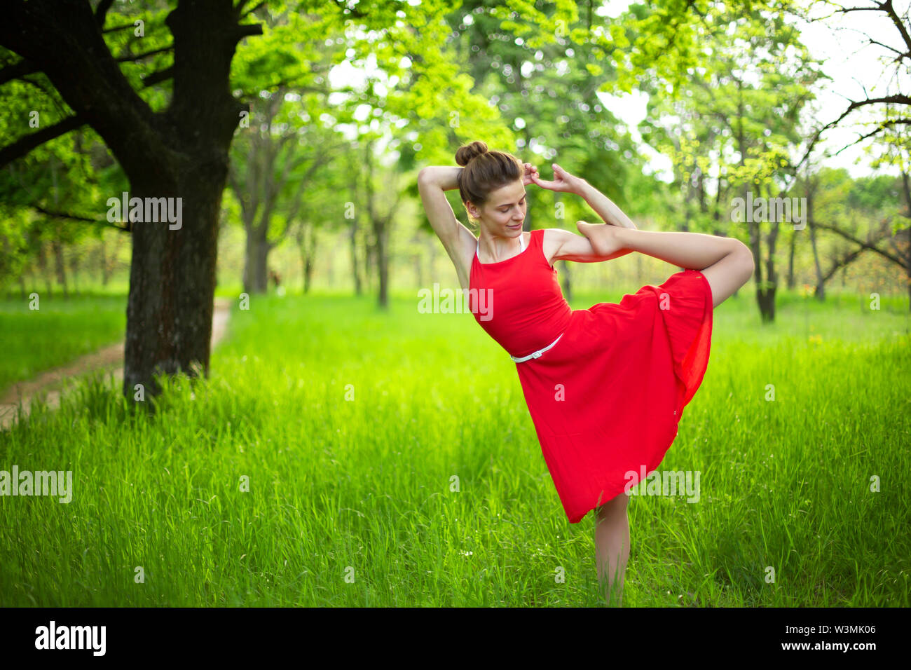 Slim beautiful brunette girl in a red dress performs yoga poses in a summer park. Green forest at sunset. - Stock Image