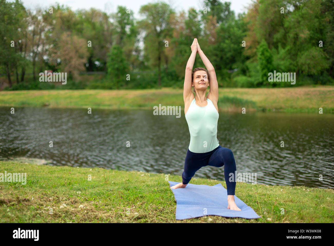 Slim brunette girl doing yoga in the summer on a green lawn by the lake. - Stock Image