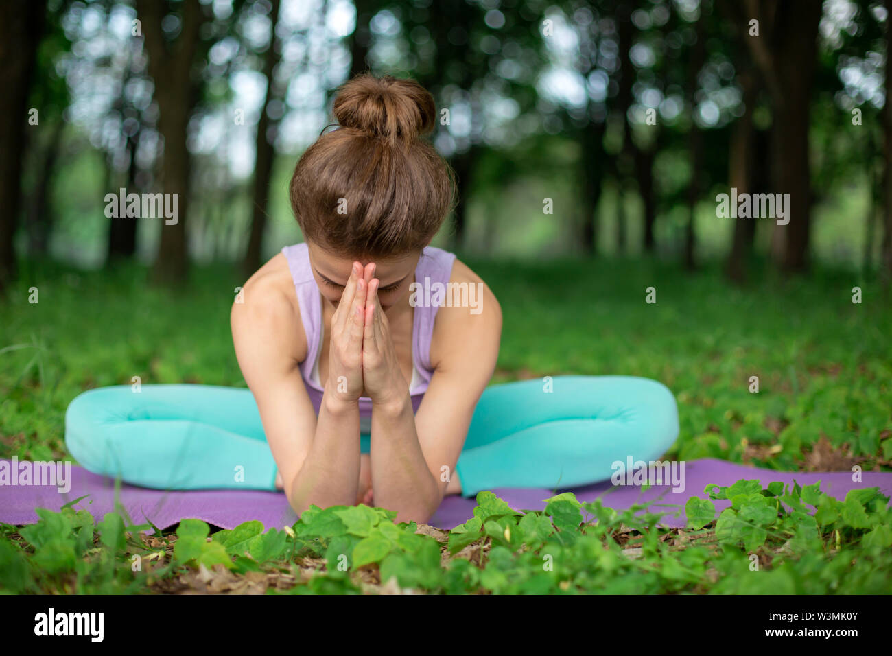Thin brunette girl plays sports and performs beautiful and sophisticated yoga poses in a summer park. Green forest on the background. Woman doing exer - Stock Image