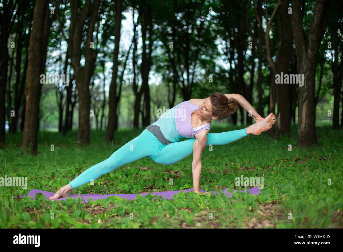 Thin brunette girl plays sports and performs beautiful and sophisticated yoga poses in a summer park. Green lush forest on the background. Woman doing - Stock Image