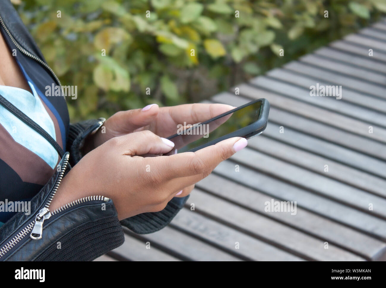 Girl holding black cellphone in her hands sitting on bench. - Stock Image