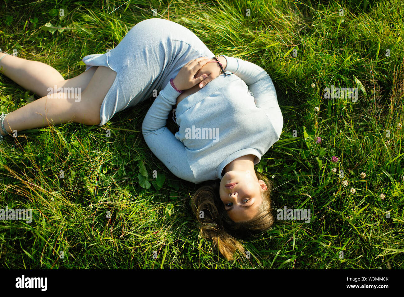 Young girl lying in green grass in the summer. Photo view from the top. - Stock Image