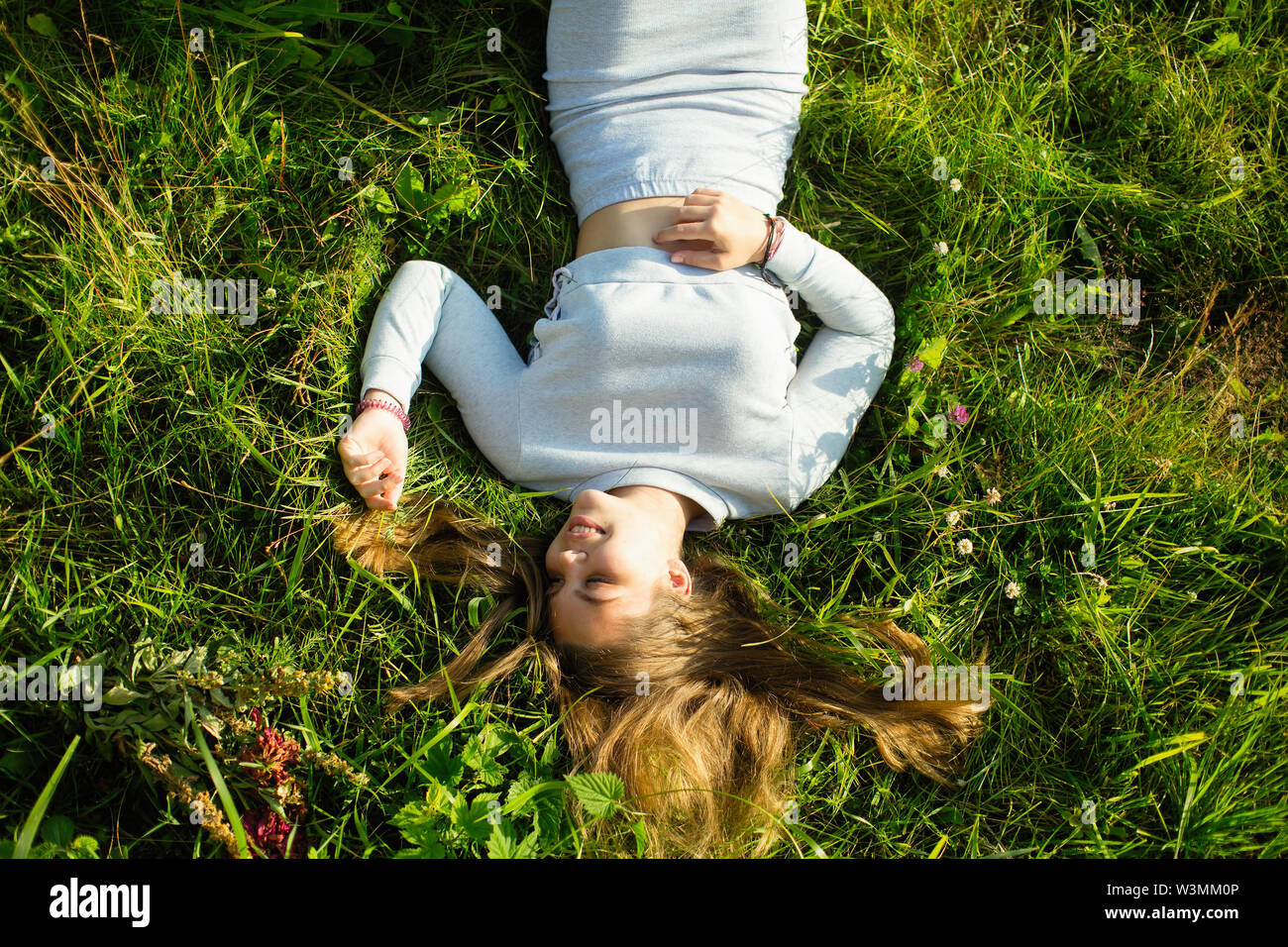 Nice girl lying in green grass in the summer. Photo view from the top. - Stock Image
