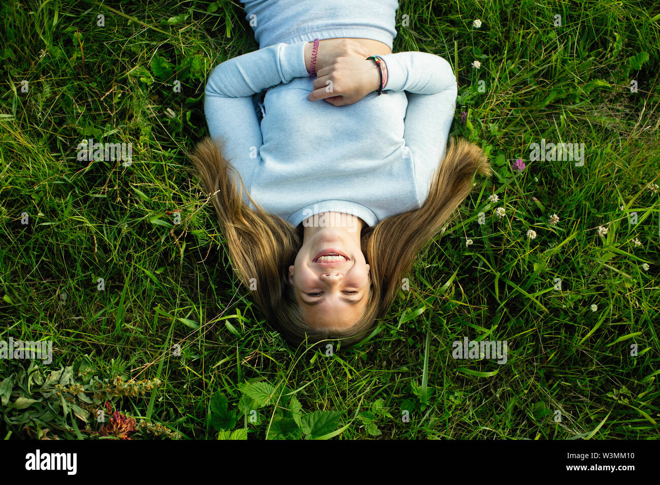 Teen girl lying in green grass in the summer. Photo view from the top. - Stock Image