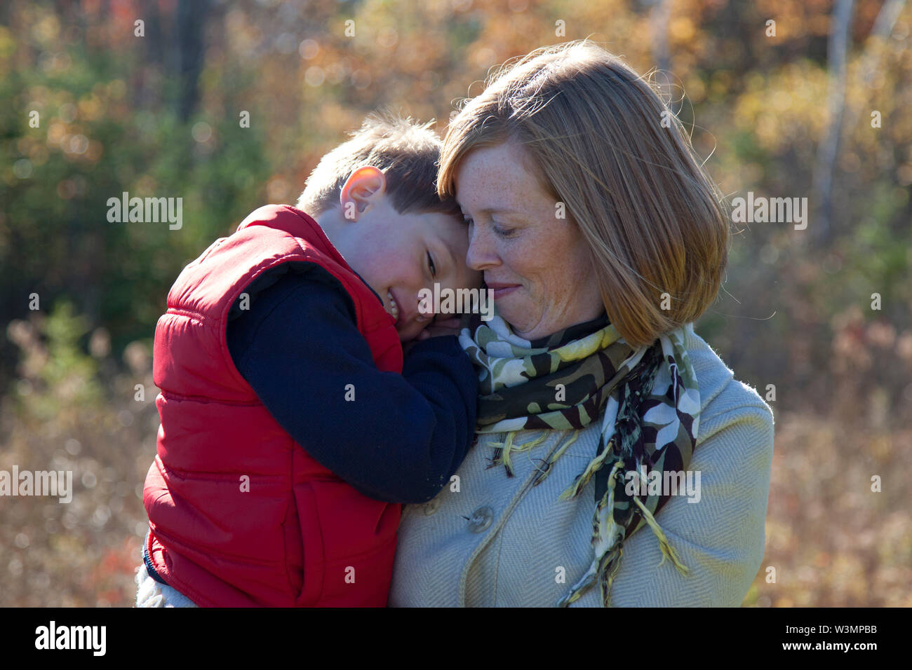 In the autumn leaves, a red haired mother holds her child close as he smiles into her shoulder - Stock Image