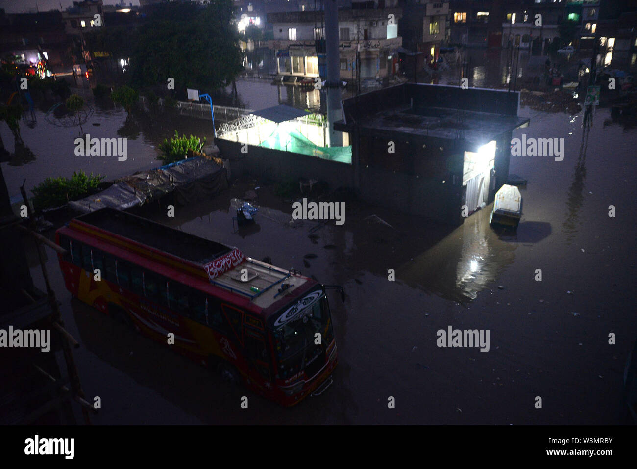 People facing troubles due to rainy water accumulated at China Scheme area as streets are presenting river view after the heavy monsoon rain in provincial. According to Met Department, heavy monsoon rain lashed Lahore and its adjoining areas in the wee hours of Tuesday. The incessant rain has flooded roads and streets in many parts of the city, rainwater entered houses in several low-lying areas of Lahore while parts of the city witnessed power outage as more that 150 Lesco feeders tripped soon after the rain started. Credit: PACIFIC PRESS/Alamy Live News - Stock Image