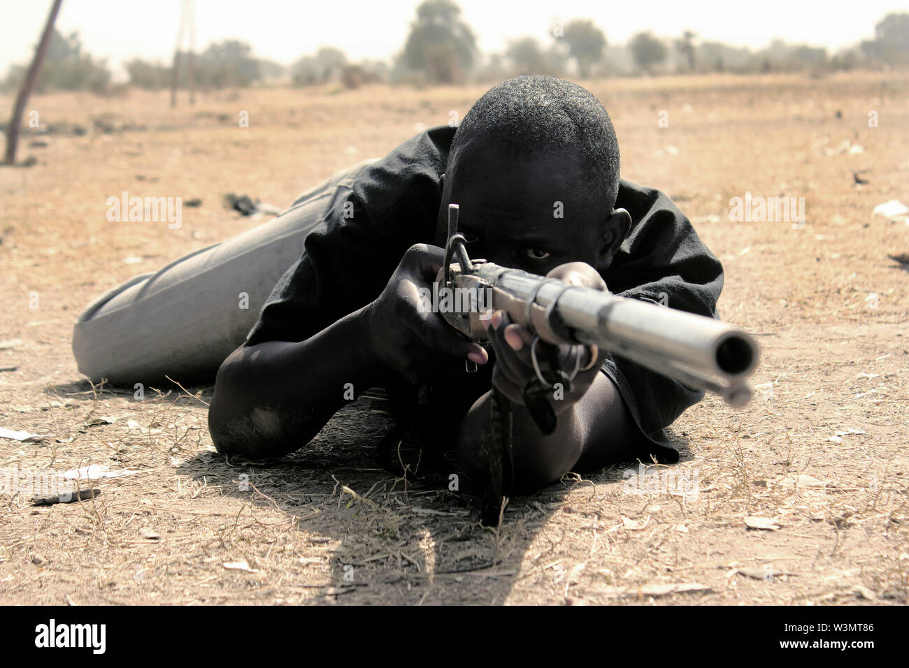 Children of returnee displaced persons are secured by local vigilantes who parade schools where learning activities take place. Siliramda Gadzama, member of the Lassa vigilante group, demonstrates how he bravely shot 50 members of Boko Haram in the Sambisa forest, Boko Haram hideout in Borno state. - Stock Image