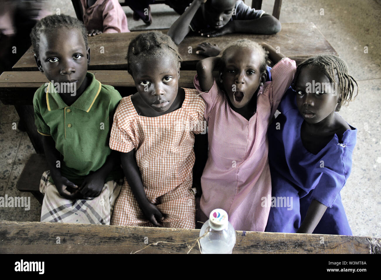 Parents of many displaced children complain of their inabilities to afford school uniforms and educational materials for their children in public school. Therefore, many of the few displaced children who attend school are encouraged to attend schools in any kind of clothes. A water bottle is the only item brought to class by these four displaced children. - Stock Image