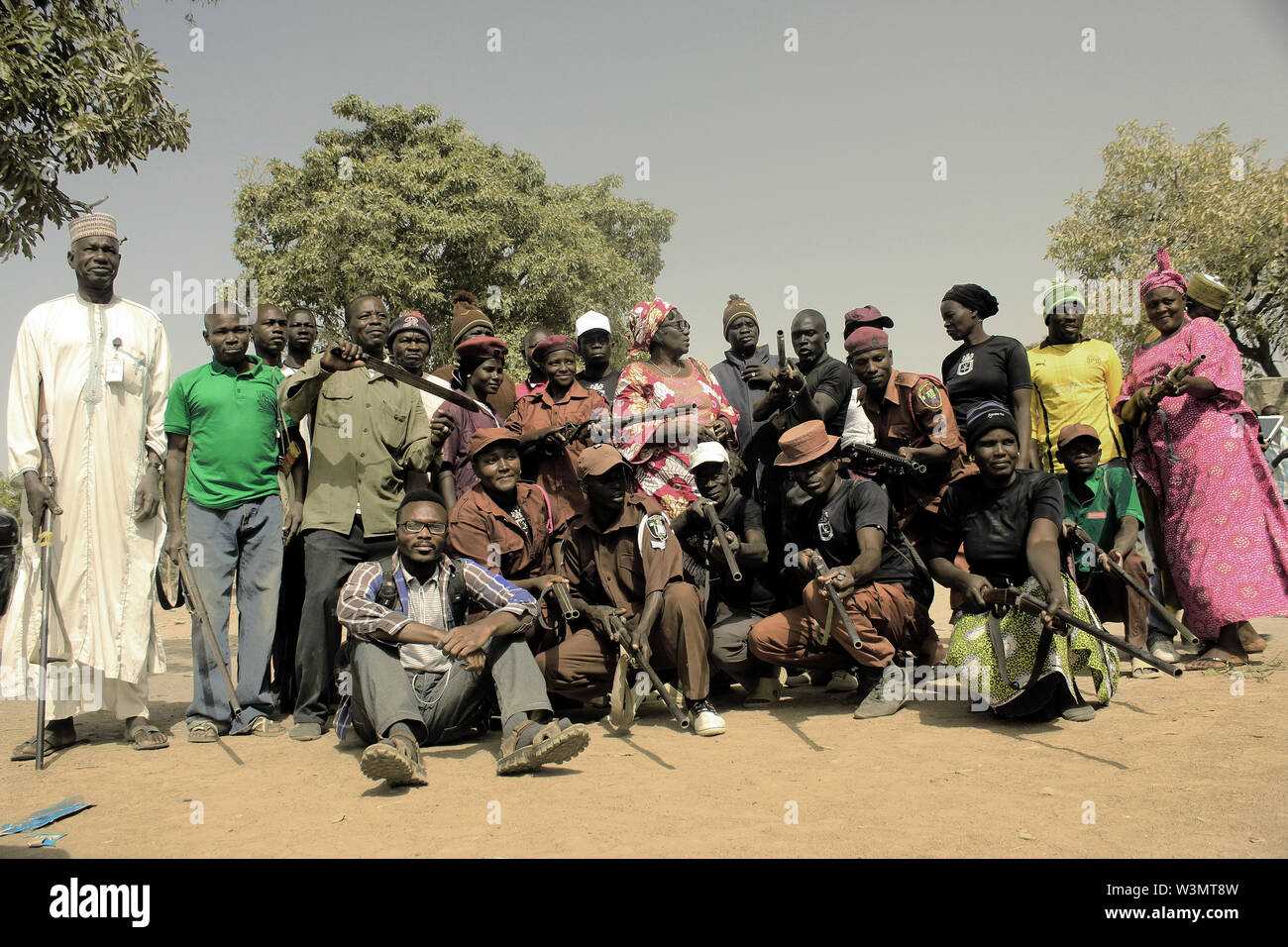 Immanuel Abayomi Afolabi, an ethnographic researcher and documentary multimedia journalist, sits with some members of Lassa vigilante group, in Borno state. - Stock Image