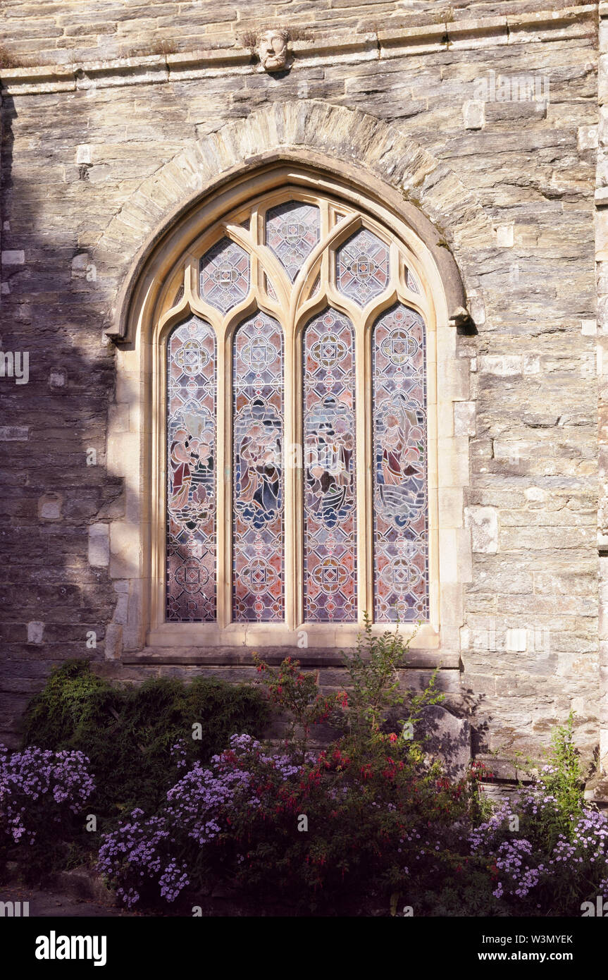 Stained glass window with tracery carving on the exterior stone walls of a church. Stock Photo