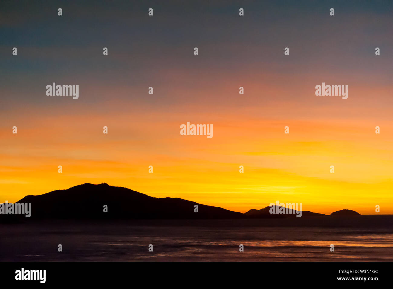 Hills silhouetted in beautiful orange and yellow sunrise, water in foreground - Stock Image