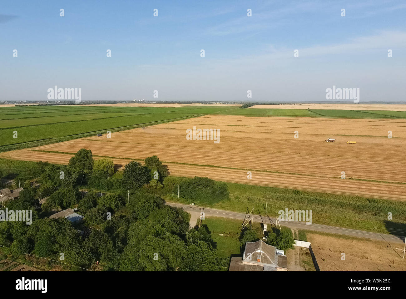 View of the field through the village. Rural landscape. Stock Photo