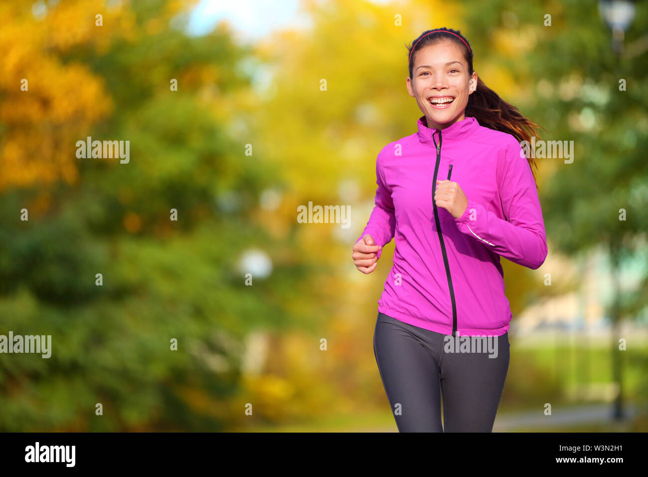 Female jogger. Fit young Asian woman jogging in park smiling happy running and enjoying a healthy outdoor lifestyle. Fitness runner girl in autumn forest with fall foliage. Mixed race Asian Caucasian. - Stock Image
