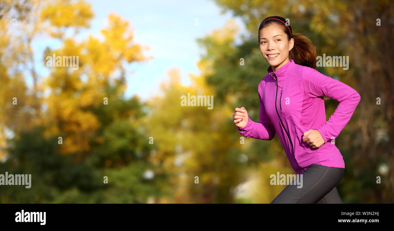 Female runner running in fall forest outside. Woman jogging looking aspirational with copy space on autumn trees. Beautilful multiracial Asian Chinese / Caucasian female fitness model training outdoor - Stock Image