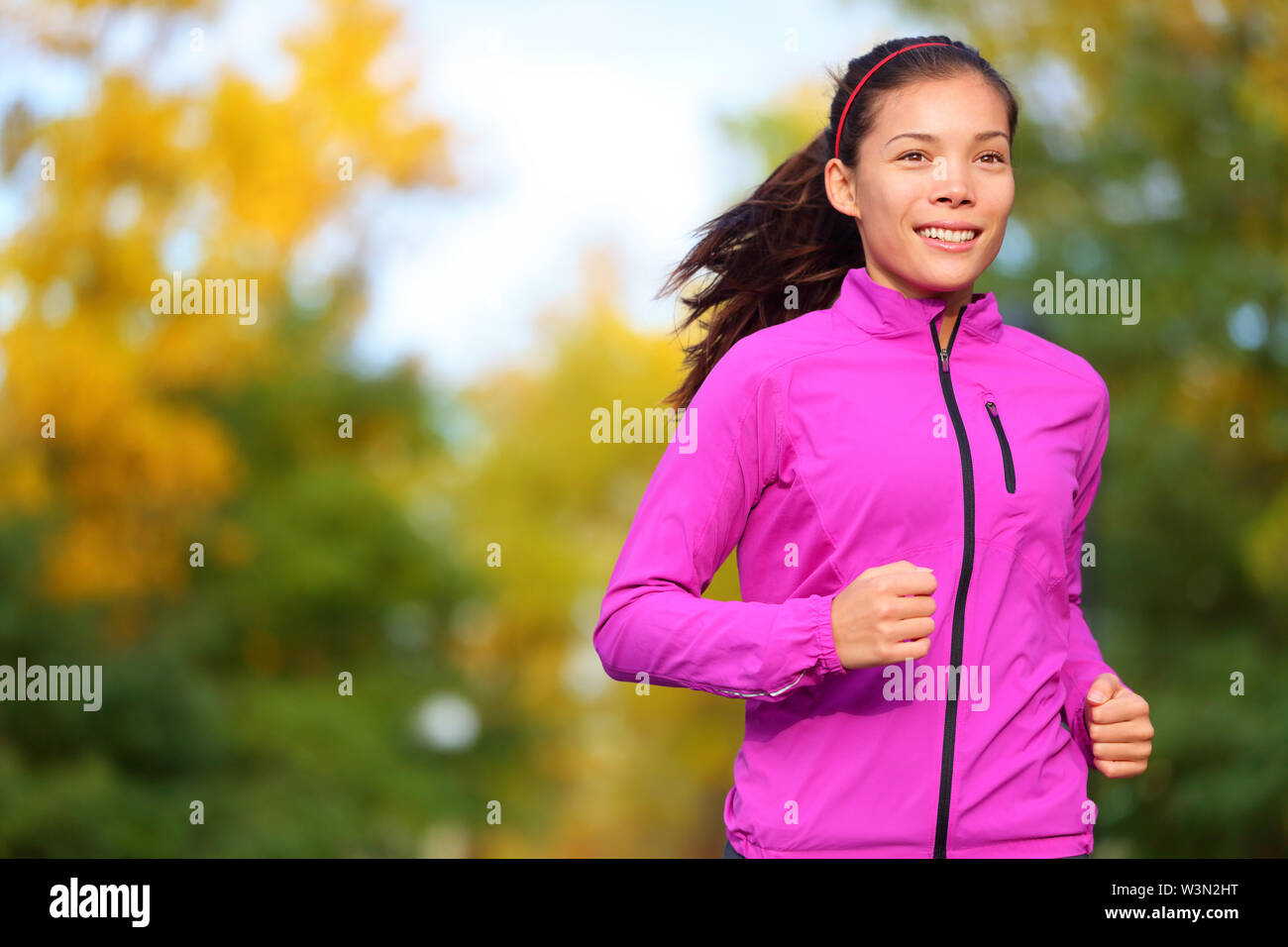 Running woman jogging in autumn forest in fall. Beautiful female runner wearing autumn running jacket. Healthy lifestyle photo with beautiful mixed race ethnic Chinese Asian and Caucasian fitness girl - Stock Image